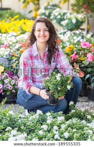Female Gardener Working at Nursery - stock photo