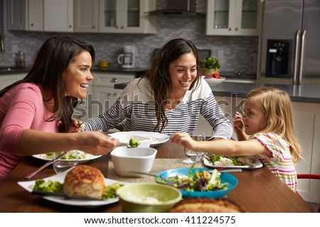 Female gay couple and daughter having dinner in their kitchen - stock photo