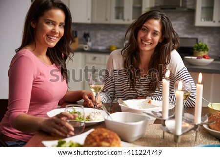 Female gay couple having dinner at home look to camera - stock photo