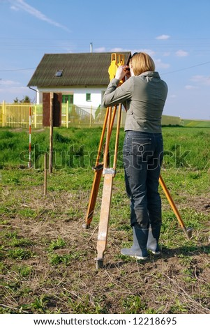 Female geodesist performing geodetic survey using altometer