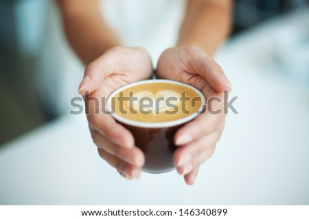 Female giving coffee with heart symbol - stock photo