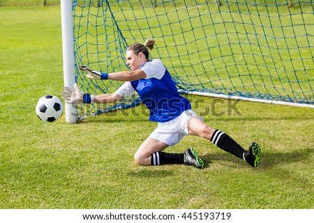 Female goalkeeper saving a goal during a game