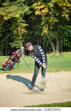 Female golf player put golf ball in sand - stock photo