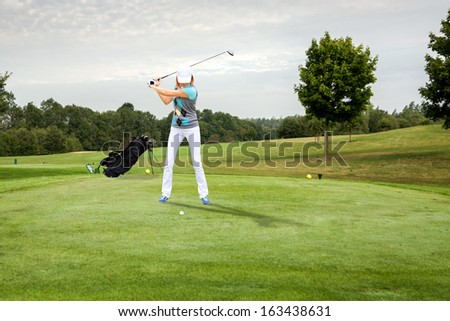 female golf player with a golf club on the course