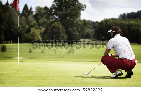 Female golf player with putter squatting to analyze the green at golf course. - stock photo