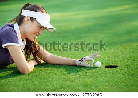 female golfer flick the golf ball into the hole - stock photo