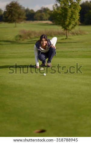 Female golfer lining up a putt kneeling on the green looking at the hole to check the grass and any camber from a slope - stock photo