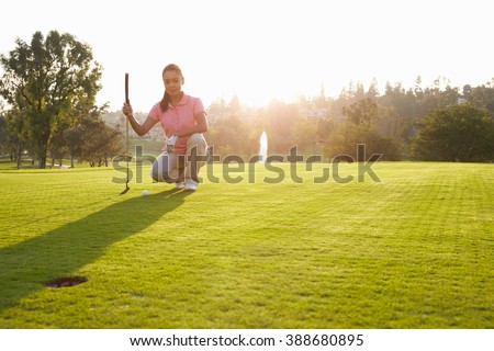 Female Golfer Lining Up Putt On Green - stock photo