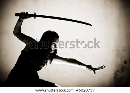 Female gothic warrior posing with katana sword. - stock photo