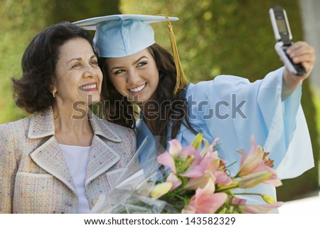 Female graduate and grandmother taking picture with cellphone outside - stock photo