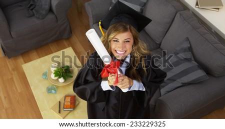 Female graduate celebrating with diploma - stock photo