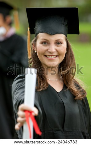 Female graduation portrait smiling and showing her diploma - stock photo