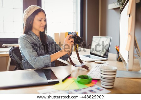 Female graphic designer looking at pictures in digital camera at office - stock photo