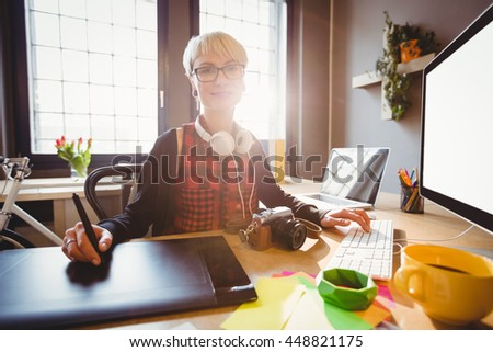 Female graphic designer using graphic tablet while working on computer at office - stock photo
