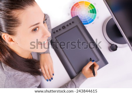 Female graphic designer working in office using tablet pen, selective focus - stock photo
