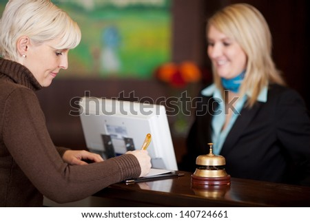female guest filling up a formular at hotel counter - stock photo