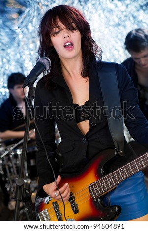 Female guitarist playing at a concert - stock photo