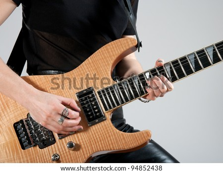 Female guitarist playing hard rock style electric guitar. - stock photo