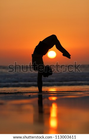 female gymnast doing a handstand in sunset at beach - stock photo