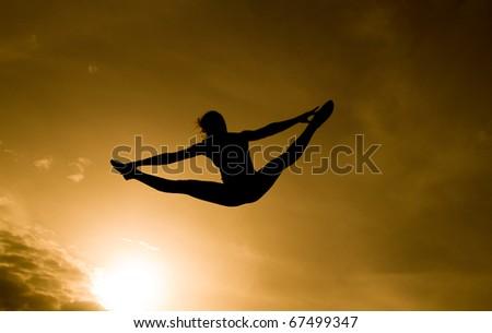 female gymnast doing the splits in golden sky - stock photo