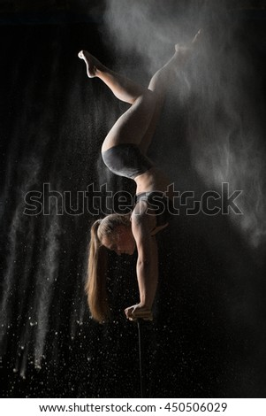 Female gymnast handstand on equilibr while sprinkled flour - stock photo