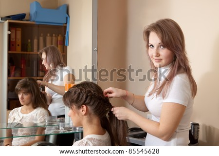Female hair stylist working with long-haired girl - stock photo