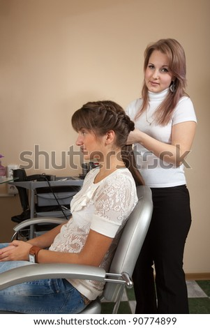 Female hair stylist working with long-haired girl