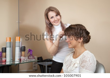 Female hair stylist working with long-haired girl. Focus on customer