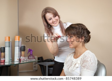Female hair stylist working with long-haired girl. Focus on customer - stock photo