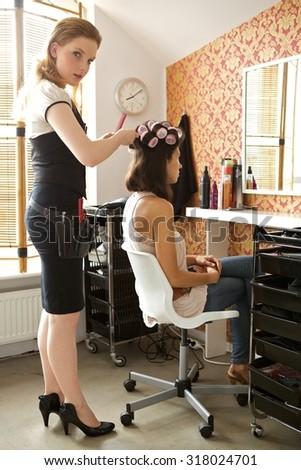 Female hairdresser adjusting curlers in young woman's hair - stock photo