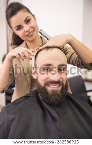 Female hairdresser cutting hair of smiling man client. - stock photo