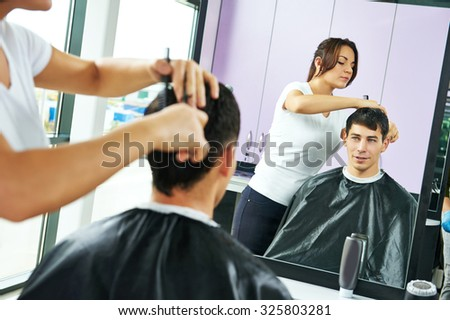 Female hairdresser cutting hair of smiling man client at beauty parlour - stock photo