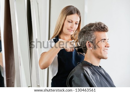 Female hairdresser cutting male client's hair in salon - stock photo