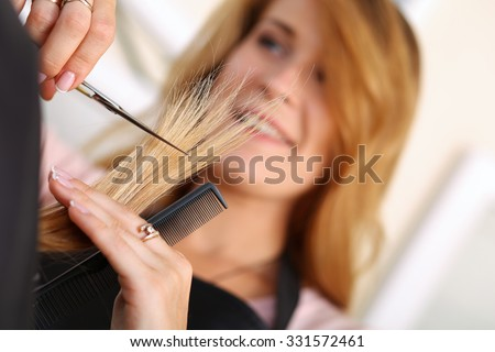 Female hairdresser hold in hand between fingers lock of hair, comb and golden scissors closeup. Hairdresser salon, barber shop, perfect look, new hairdo concept