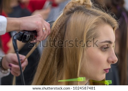 Female hairdresser standing and making hairstyle to cute lovely young blonde woman in beauty salon