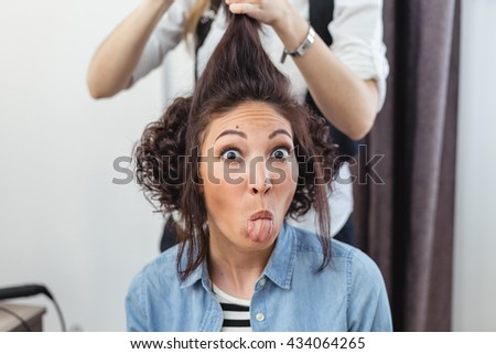 Female hairdresser standing and making hairstyle to cute lovely young yelling woman in beauty salon - stock photo