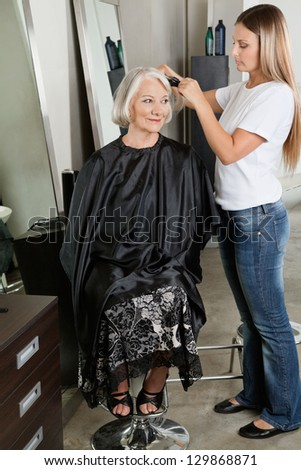Female hairdresser straightening senior woman's hair at beauty parlor