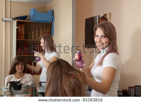 Female hairdresser working with long-haired girl - stock photo