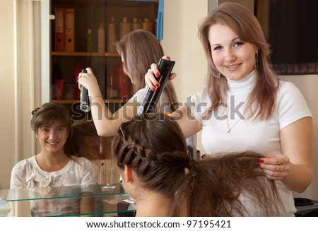 Female hairdresser works on woman hair in salon