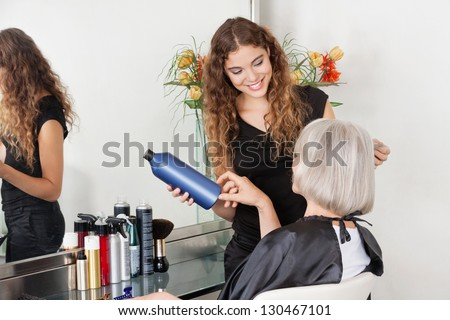 Female hairstylist advising hair color to senior client at beauty parlor