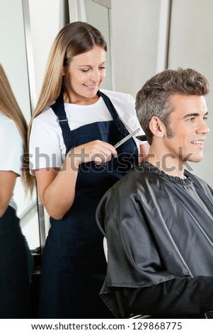 Female hairstylist giving haircut to mature client at hair salon - stock photo
