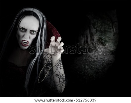 Female Halloween Vampire inside a cave. Girl with dripping blood from her red lips. Vampire makeup and costume for Halloween party. Dark background with copy space