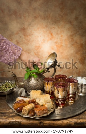 Female hand adding mint leaves on a Moroccan tea tray - stock photo