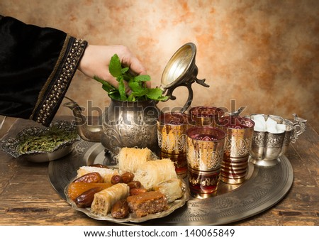 Female hand adding mint leaves to a tray with dates, cookies and tea the moroccan style - stock photo