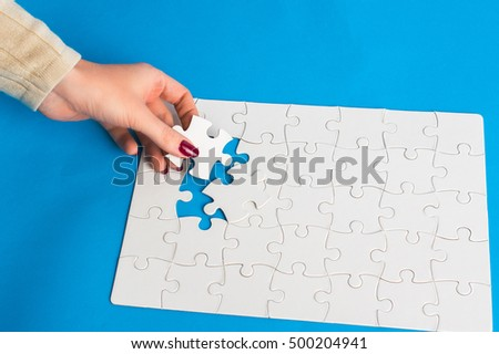 Female hand adds white puzzle. On a blue background.