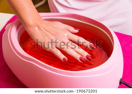 Female hand and orange paraffin wax in bowl. Manicure and skincare. Woman girl in beauty spa salon. - stock photo