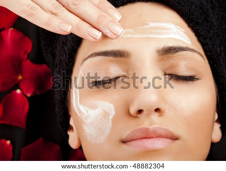 female hand applying moisturizing cream on a woman?s face - stock photo
