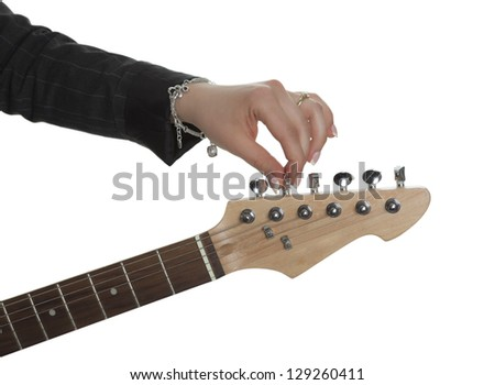 Female hand at an electric guitar