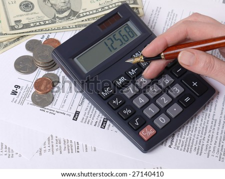 Female hand calculating taxes on calculator with W-9 income tax forms underneath - stock photo