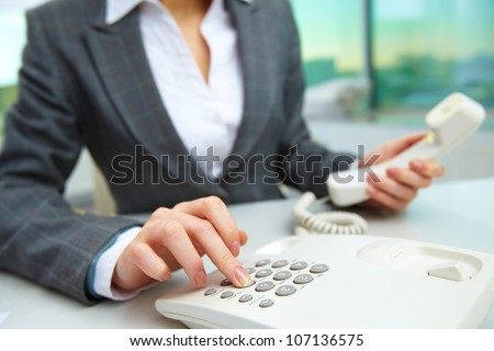 Female hand dialing number in office - stock photo
